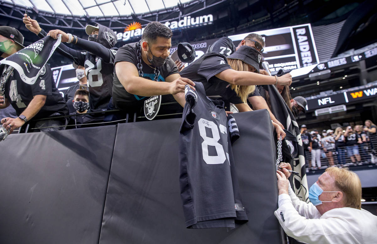 Raiders owner Mark Davis signs autographs for fans before the Raiders home opening preseason ga ...