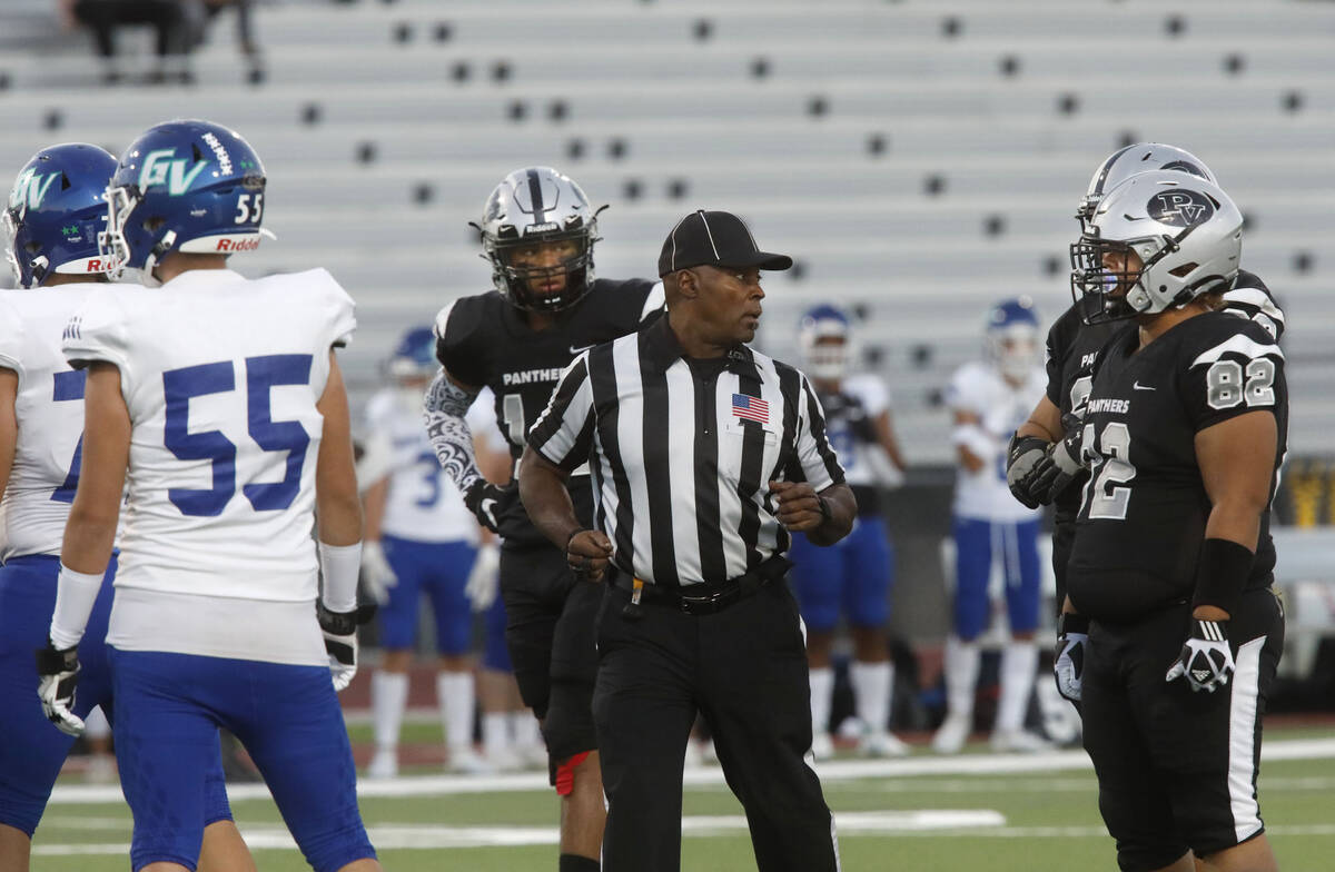 Umpire Gordon Washington, center, talks to players during the first half of a football game bet ...