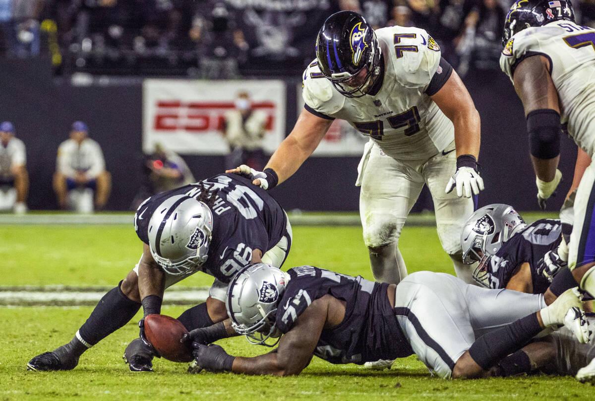 Raiders defensive tackle Darius Philon (96) picks up a fumble with teammate Raiders defensive e ...