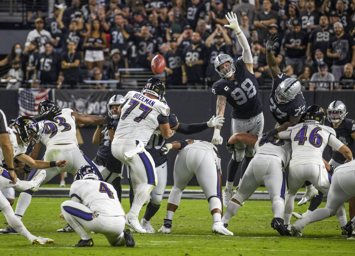 Raiders defensive end Maxx Crosby (98) gets up high to attempt a field goal block during the th ...