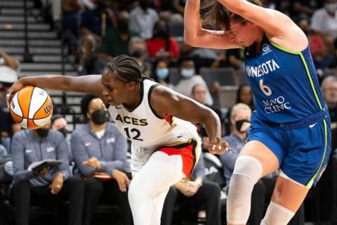 Las Vegas Aces guard Chelsea Gray (12) dribbles toward the hoop while Minnesota Lynx forward Br ...