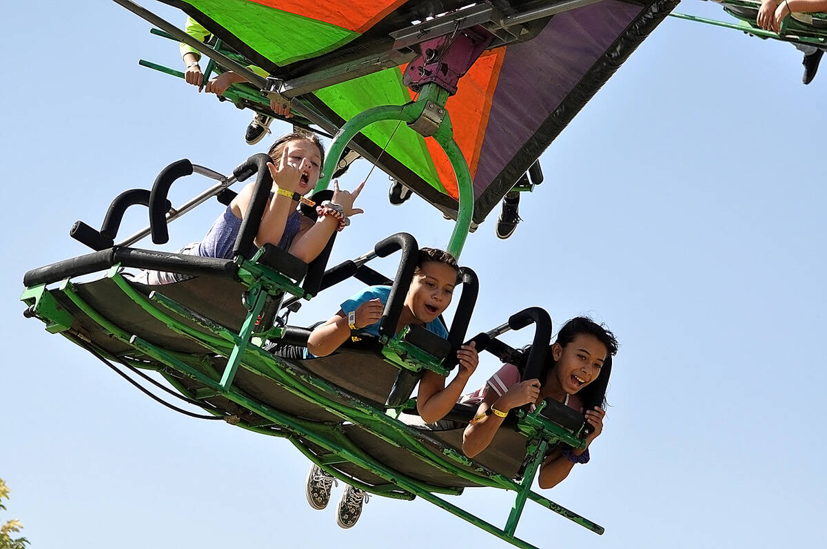 Horace Langford Jr./Pahrump Valley Times Three young individuals fly high above the carnival g ...