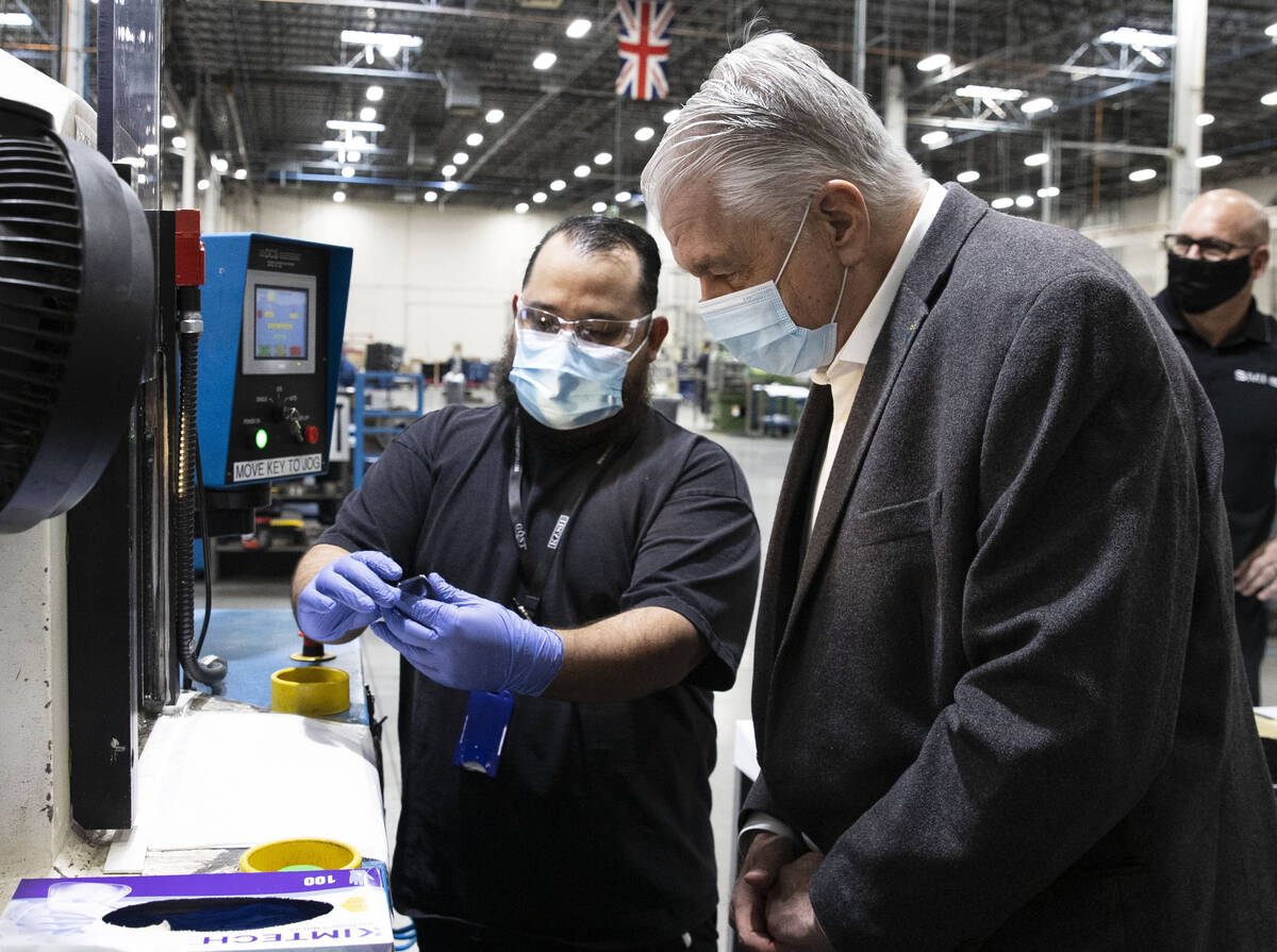 Federico Rincon, left, a supervisor at Sunshine Minting, shows a final silver product to Gov. S ...