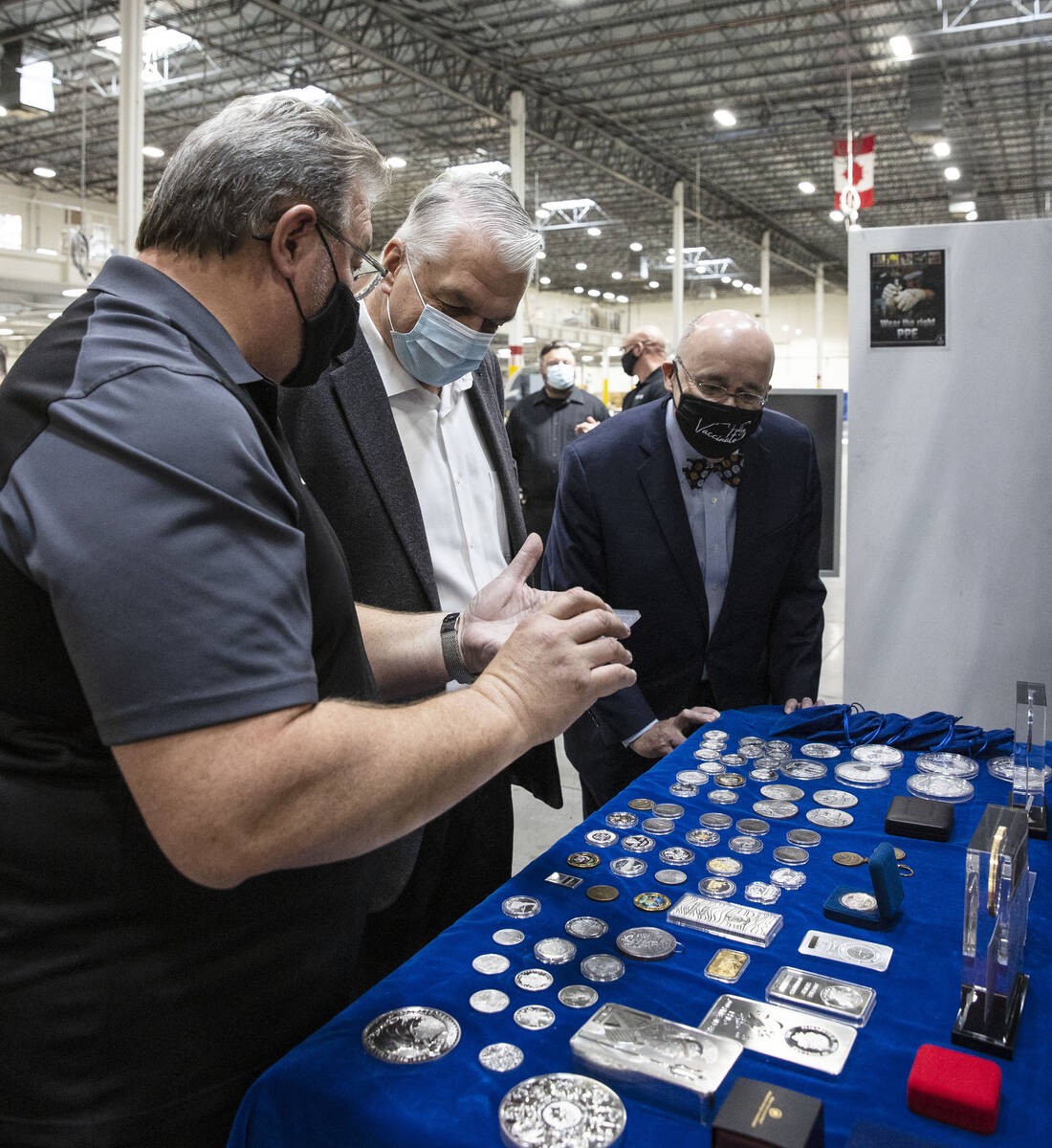 Gov. Steve Sisolak, center, and Michael Brown, right, executive director of the Nevada Governor ...