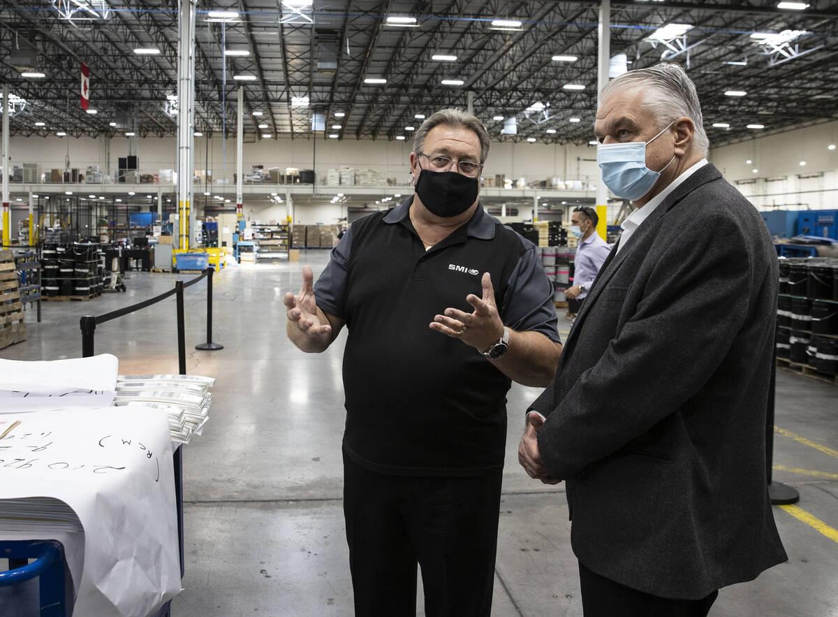 Gov. Steve Sisolak listens to Thomas Power, left, president and CEO of Sunshine Minting Inc., d ...