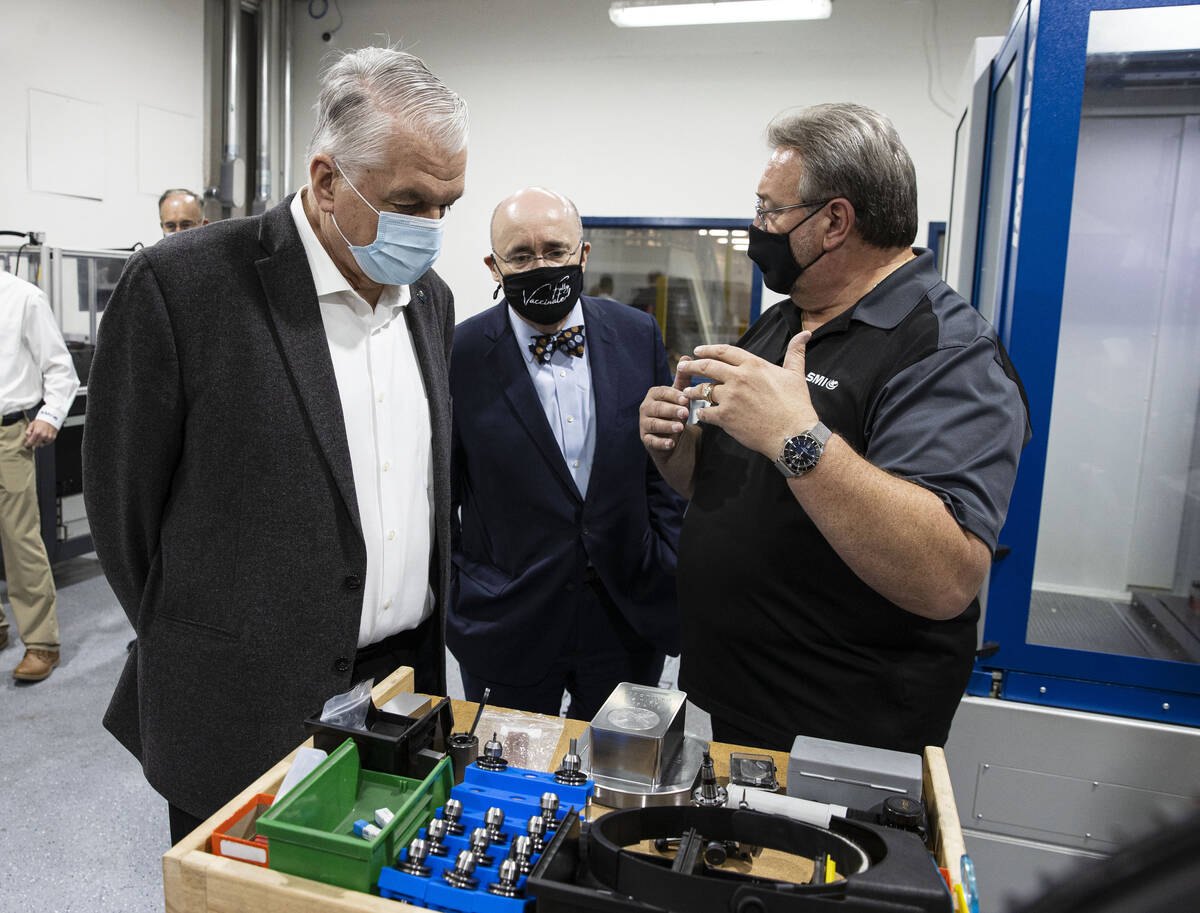 Gov. Steve Sisolak, left, and Michael Brown, center, executive director of the Nevada Governor' ...