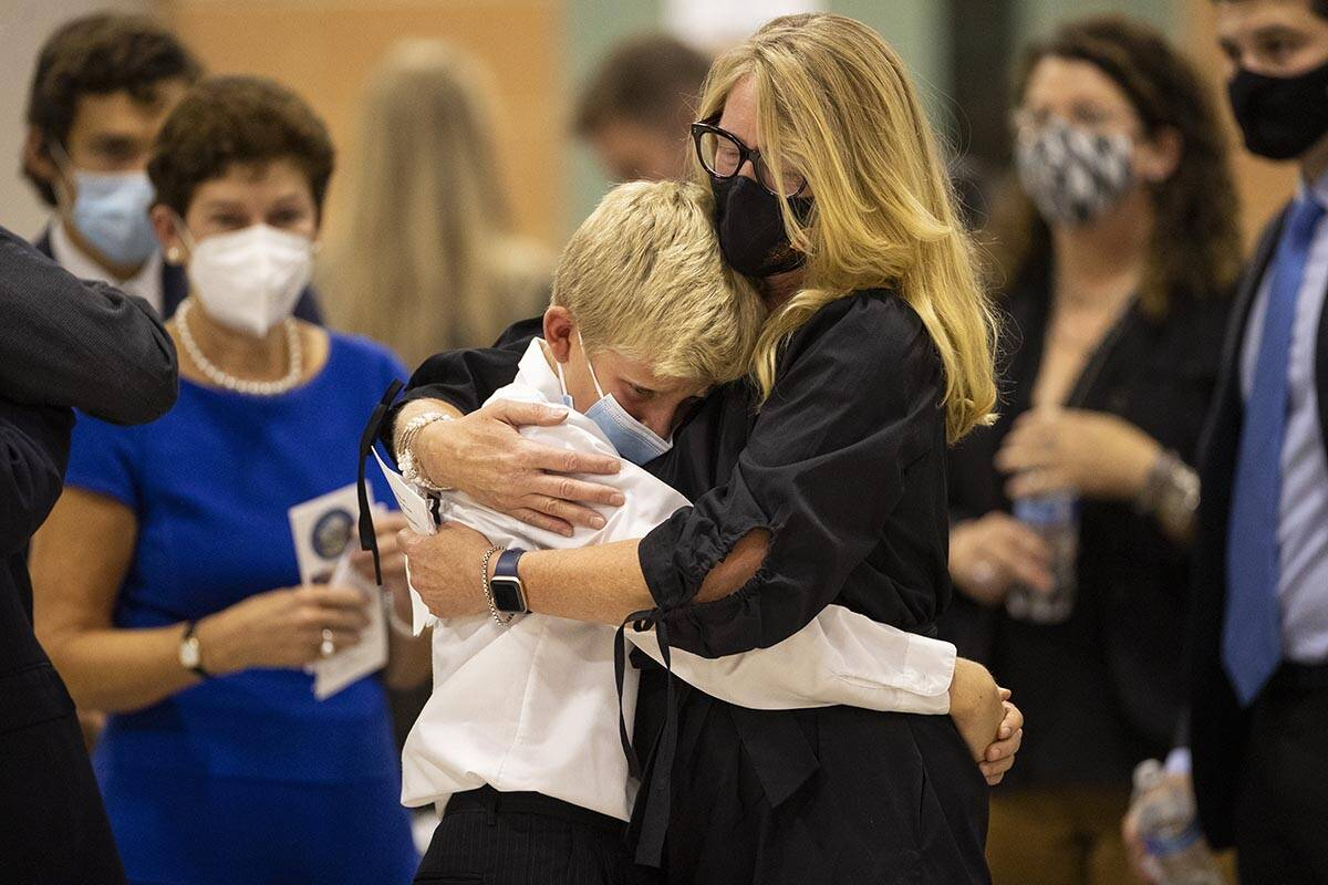 Karen Wayland, right, hugs her nephew Levi, 11, during a ceremony to honor the memory of her l ...